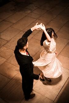Homem jovem, segurando mão, de, whirling, elegante, mulher