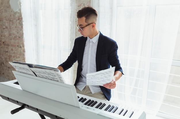 Homem jovem, segurando, musical, folha, tocando, piano, sentar, perto, a, janela