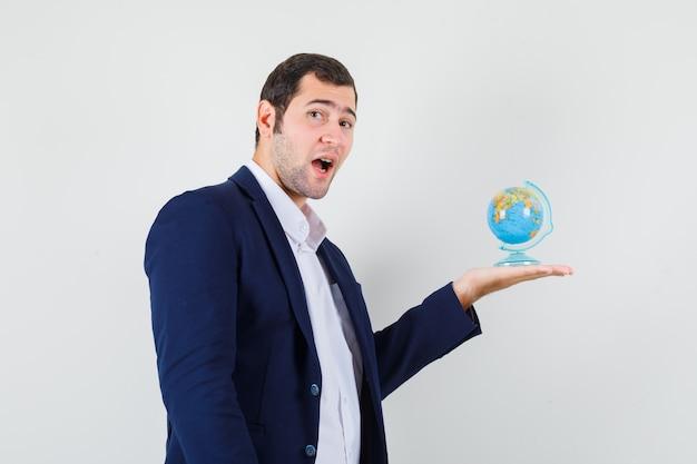 Homem jovem segurando o globo da escola com camisa e jaqueta e parecendo pensativo