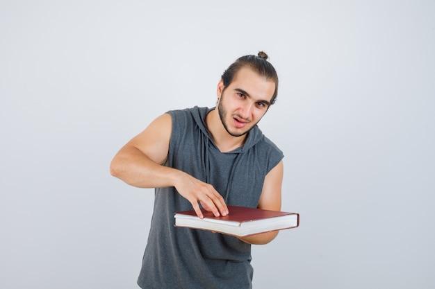 Homem jovem segurando o livro com capuz sem mangas e parecendo confiante, vista frontal.