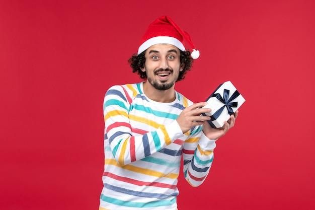 Homem jovem segurando o presente de ano novo de frente nas emoções do feriado de ano novo de fundo vermelho