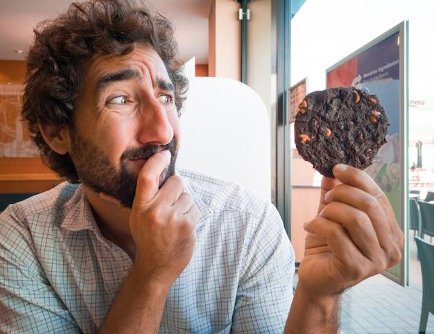 Homem jovem, segurando, um, biscoito chocolate, em, um, loja café