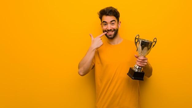Homem jovem, segurando, um, troféu, sorrisos, apontando boca