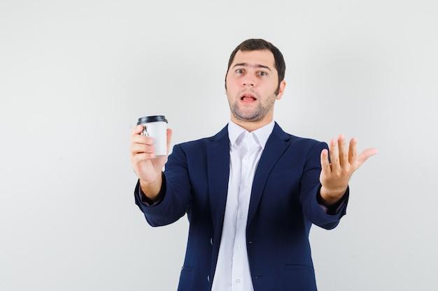 Homem jovem segurando uma xícara de café com uma camisa, jaqueta e parecendo confuso