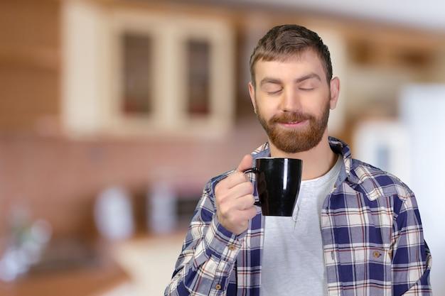 Homem jovem, segurando, xícara morna, de, tea / coffee