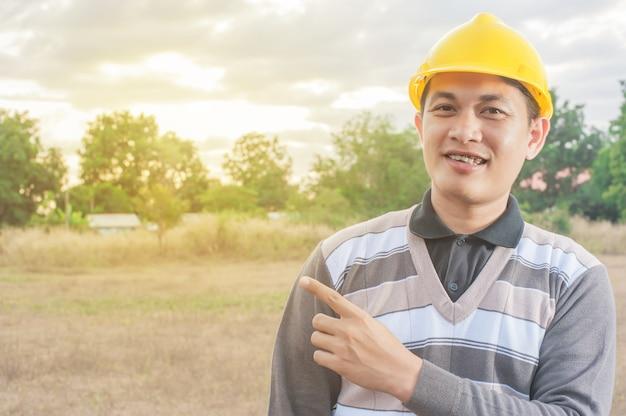 Homem jovem, segure, chapéu, segurança, engrenagem, e, workwear, construção