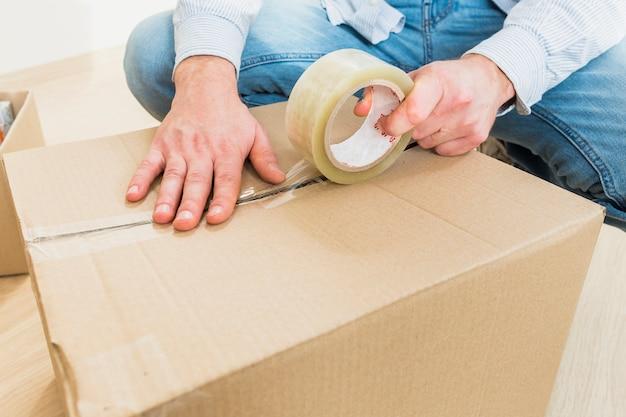 Homem jovem, selando, caixa papelão, com, fita, grande, para, em movimento