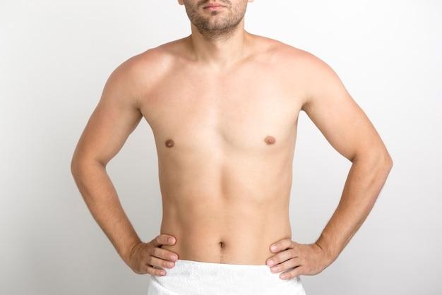 Homem jovem sem camisa, mantendo as mãos na cintura e posando