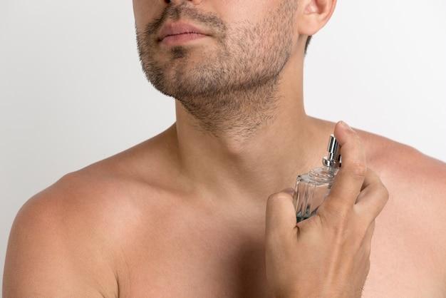 Homem jovem sem camisa, pulverizando perfumes em fundo branco
