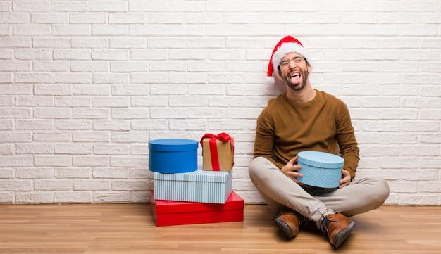 Homem jovem, sentando, com, presentes, celebrando, funnny natal, e, amigável, mostrando, língua