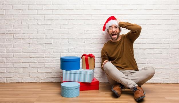 Homem jovem, sentando, com, presentes, celebrando, natal, forgetful, realize algo