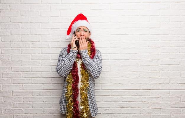 Homem jovem, sentando, com, presentes, celebrando, natal, muito, assustado, e, amedrontado, escondido