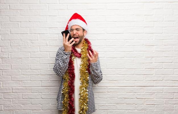 Homem jovem, sentando, com, presentes, celebrando, natal, muito, assustado, e, amedrontado