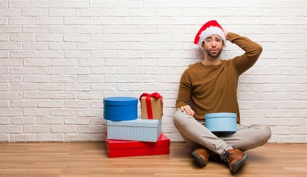 Homem jovem, sentando, com, presentes, celebrando, natal, preocupado, e, oprimido
