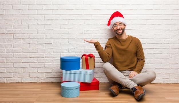 Homem jovem, sentando, com, presentes, celebrando, natal, segurando, algo, com, mão