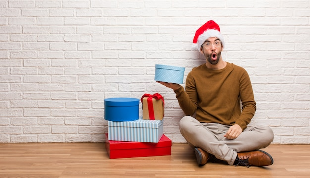 Homem jovem, sentando, com, presentes, celebrando, natal, segurando, algo, ligado, palma, mão