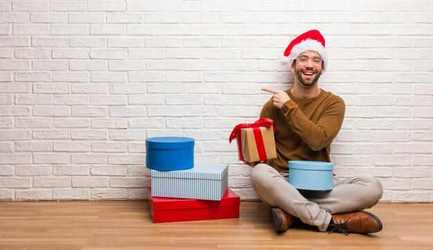 Homem jovem, sentando, com, presentes, celebrando, natal sorrindo, e, apontar, ao lado