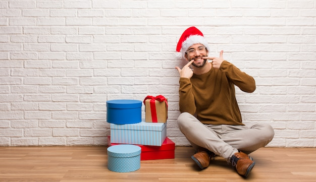 Homem jovem, sentando, com, presentes, celebrar, sorrisos natal, apontando boca