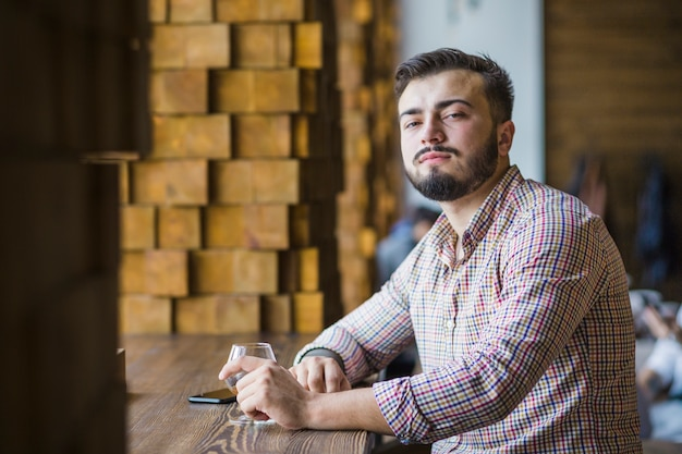 Homem jovem, sentando, em, restaurante, com, vidro, de, bebida