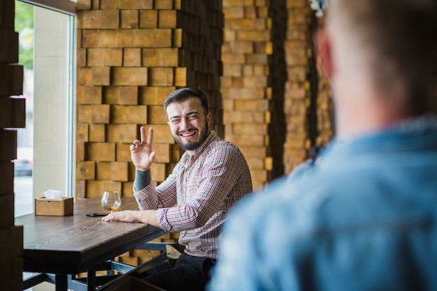 Homem jovem, sentando, em, restaurante, dizendo olá, para, seu, amigo