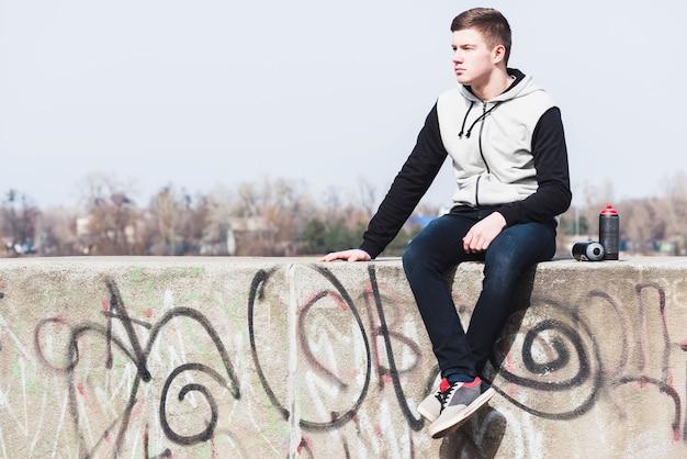 Homem jovem, sentando, ligado, parede graffiti
