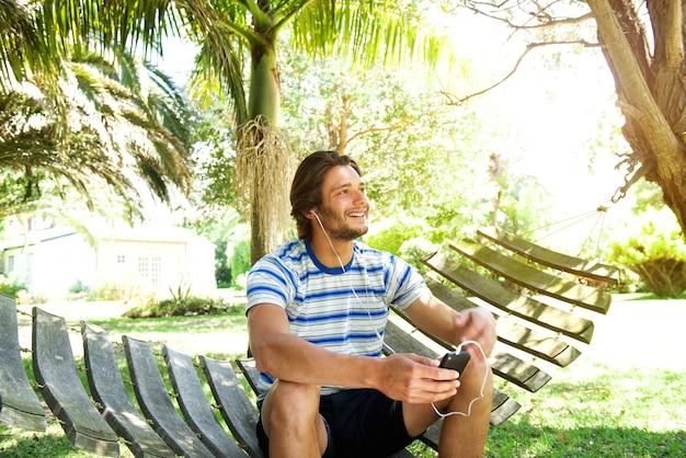 Homem jovem, sentando rede, escutar música