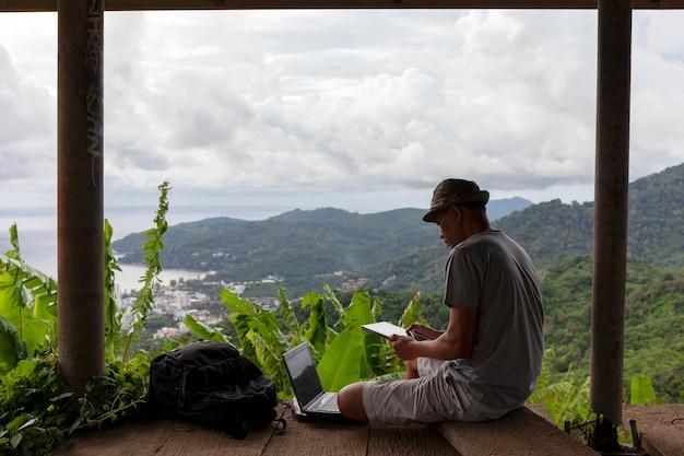 Homem jovem, sentando, usando computador portátil, contra, paisagem, paisagem, floresta, e, andaman, mar, em, phuket, tailandia