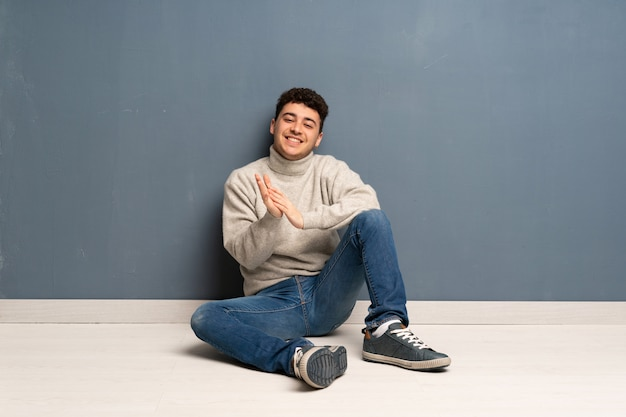 Homem jovem, sentar chão, aplaudindo, após, apresentação, em, um, conferência