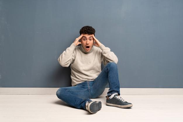 Homem jovem, sentar chão, com, expressão surpresa