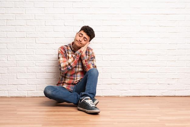 Homem jovem, sentar chão, fazer, sono, gesto, em, dorable, expressão