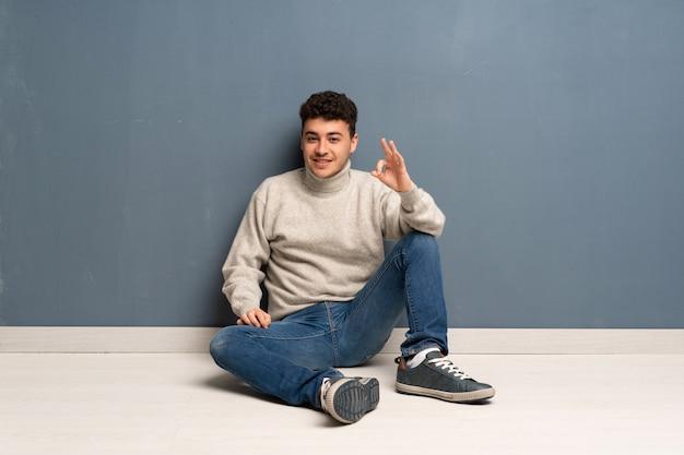 Homem jovem, sentar chão, mostrando, tá bom sinal, com, dedos