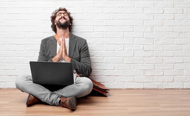 Homem jovem, sentar chão, orando, em, um, santamente, maneira, implorando