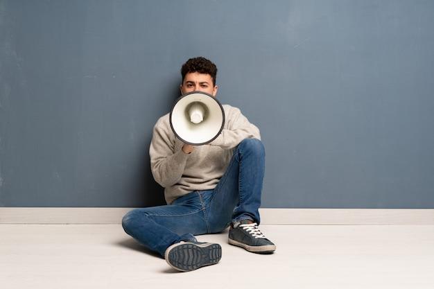 Homem jovem, sentar chão, shouting, através, um, megafone