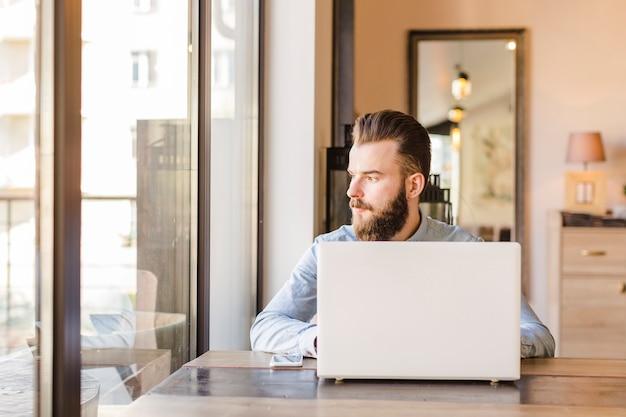 Homem jovem, sentar restaurante, com, laptop, e, cellphone, escrivaninha