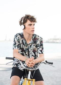 Homem jovem, sentar-se bicicleta, escutar música