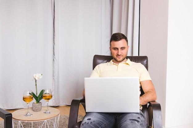 Homem jovem, sentar-se cadeira, usando computador portátil, com, wineglasses, ligado, tabela