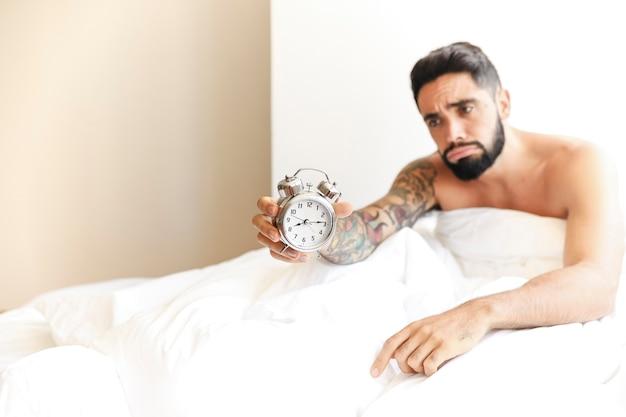 Homem jovem, sentar-se cama, segurando, despertador