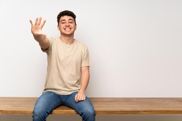 Homem jovem, sentar-se tabela, contando cinco, com, dedos