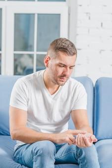 Homem jovem, sentar sofá azul, verificar, seu, pulso
