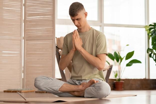 Homem jovem, sereno e concentrado, ativo, mantendo as mãos unidas pela cabeça baixa enquanto pratica a meditação no tapete em casa