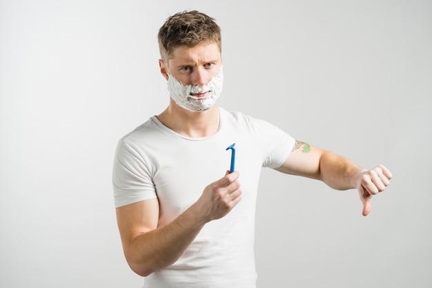 Homem jovem sério com espuma de barbear no rosto, segurando a navalha azul na mão, mostrando os polegares para baixo, contra um fundo cinza