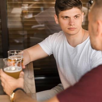Homem jovem sério com seus amigos bebendo cerveja