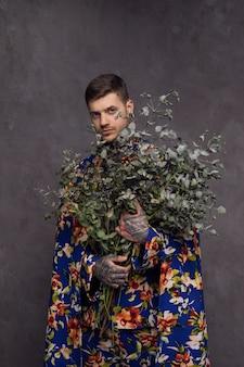 Homem jovem sério com tatuagem na mão segurando galhos de planta