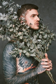 Homem jovem sério com tatuagem no corpo dele segurando galhos de planta sob o rosto