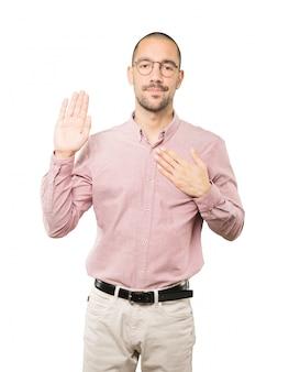 Homem jovem sério com um gesto de juramento