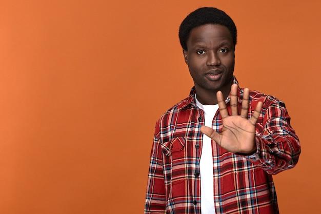 Homem jovem sério de pele escura confiante mostrando o sinal de pare, levantando a palma da mão aberta e dizendo não. africano elegante fazendo gesto de aviso de recusa com a mão na frente dele, expressando recusa