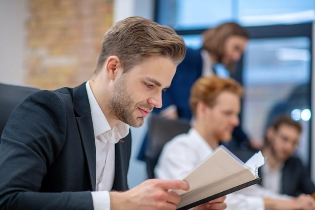 Homem jovem sério e atencioso de perfil em terno lendo documento atentamente enquanto está sentado com colegas no escritório