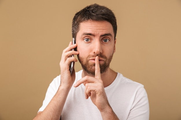 Homem jovem sério e casual falando no celular isolado, mostrando gesto de silêncio