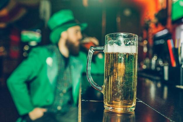 Homem jovem sério e concentrado no terno de são patrício sentado no balcão do bar sozinho. caneca de cerveja parada na frente dele, perto da câmera