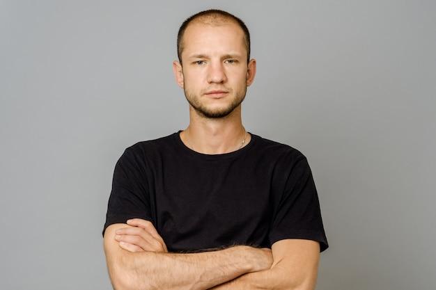 Homem jovem sério em camiseta preta com braços cruzados